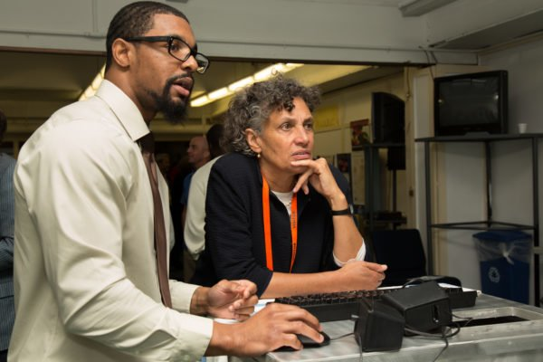 BPI student showing New York Department of Public Health Commissioner Mary Bassett something on a computer.