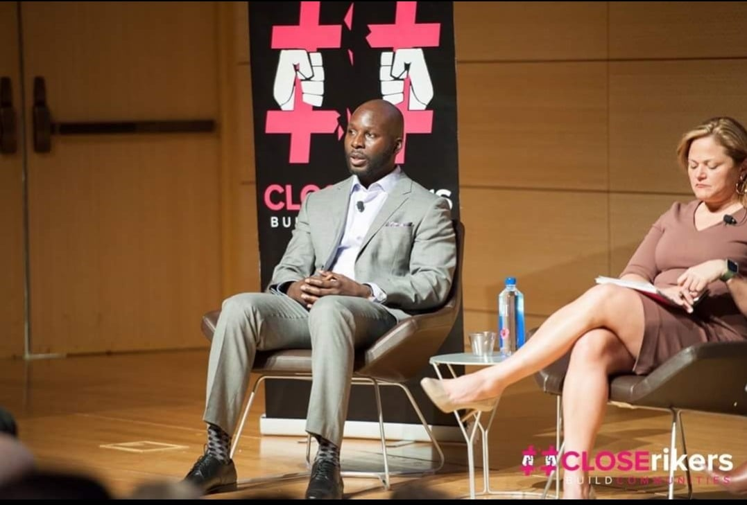 BPI alumnus sitting onstage at a #CloseRikers event.