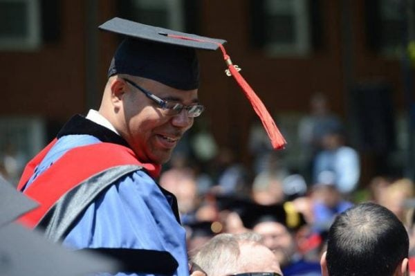 BPI alumnus smiling in cap and gown at the BPI commencement.