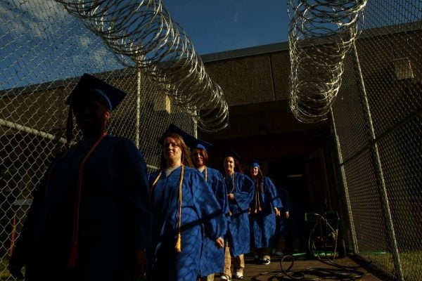 Women in Cap and Gown walk through Washington Corrections Center for Women