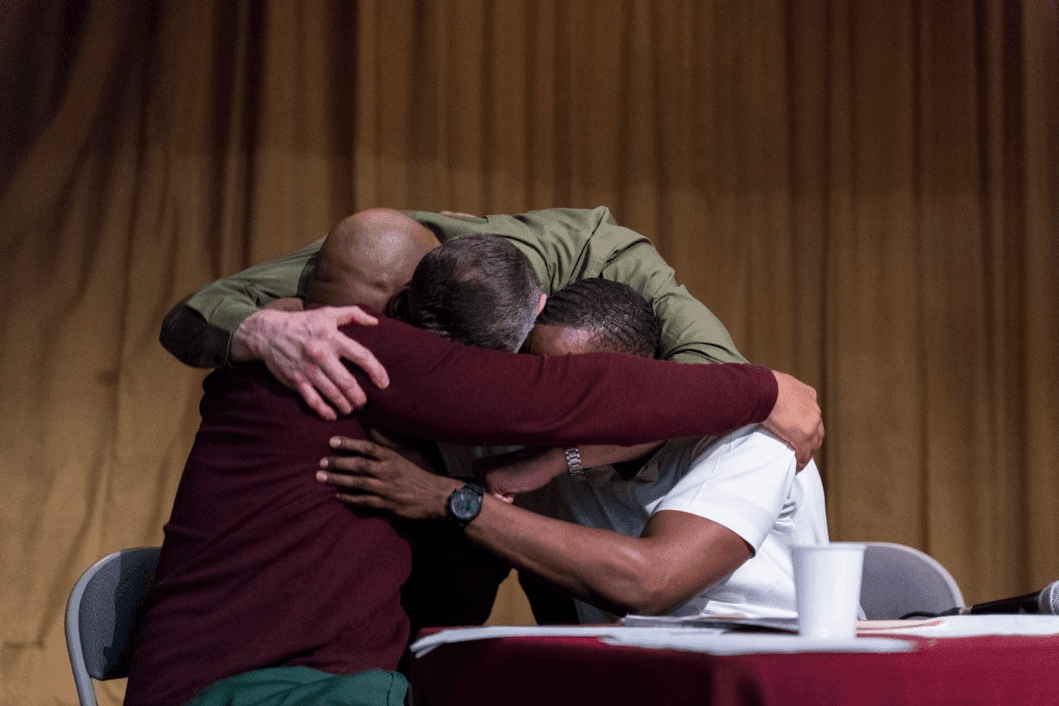 The Bard Prison Initiative team hugs in reaction to defeating Cambridge.