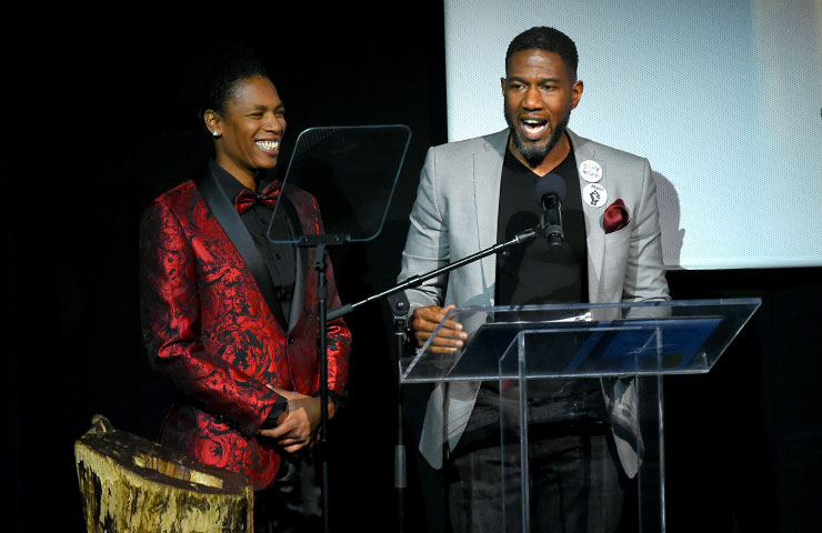 Tamika Graham smiling and standing next to Jumaane Williams as he speaks on stage.