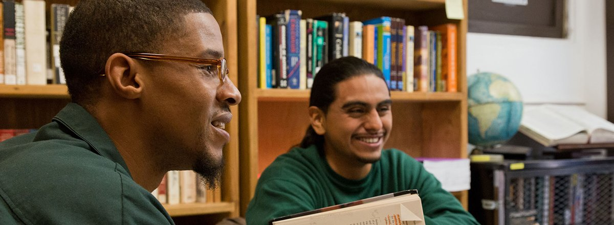 BPI Students smiling and having a discussion in the library.