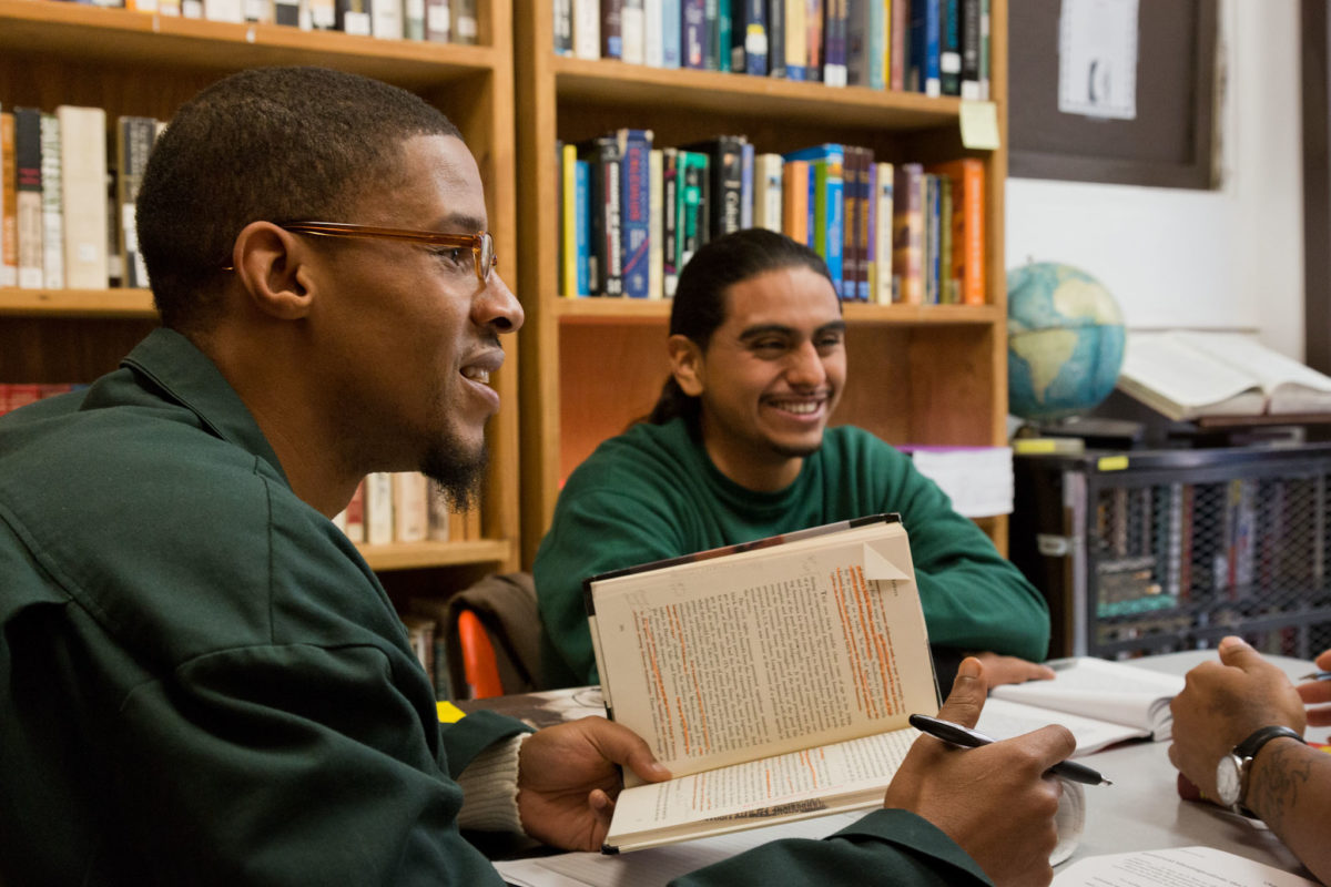 BPI students discuss a book in the library
